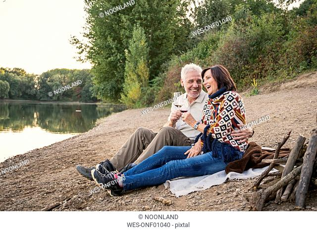 Happy senior couple with wine at a lake in the evening
