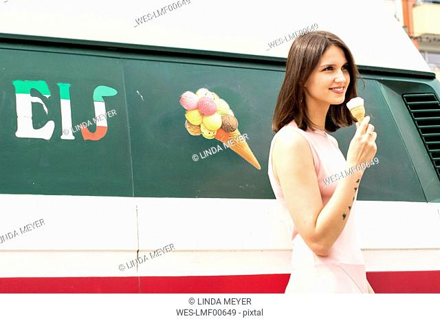 Smiling young woman with ice cream cone in front of ice cream van