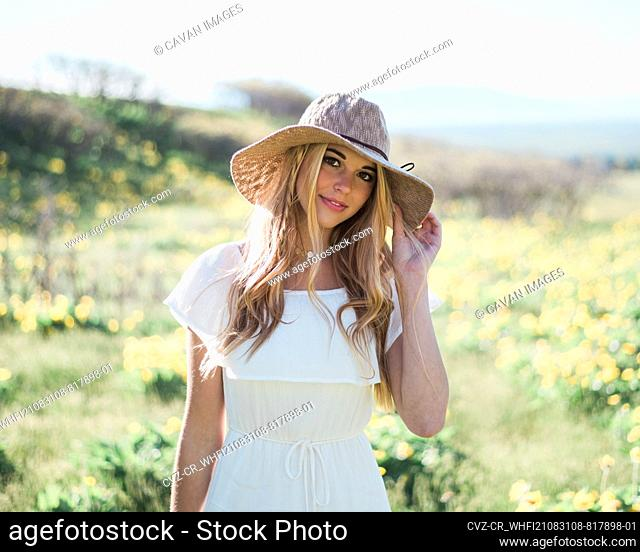 Young Blonde Woman with Summer Beach Hat in Field of Flowers