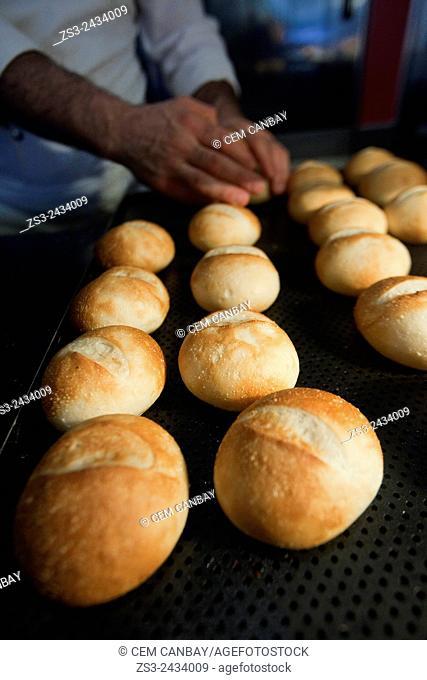 Turkish cook organizing fresh breads on the tray, Taksim, Istanbul, Turkey, Europe