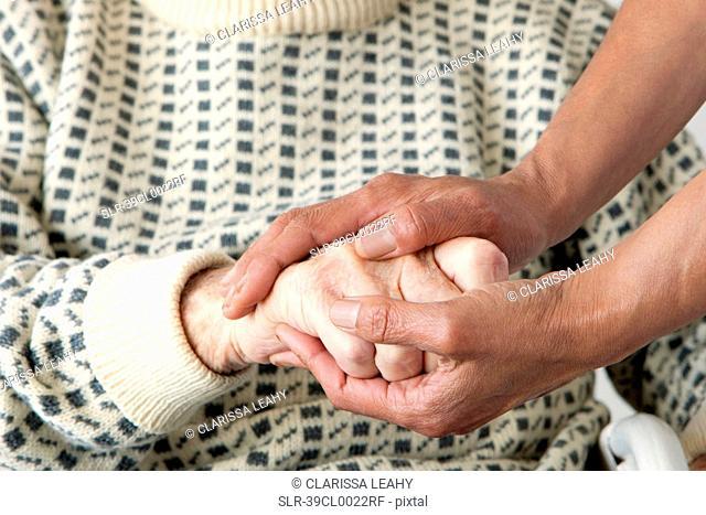 Caretaker patting older man?s hand