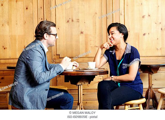 Man and woman sitting in cafe drinking coffee