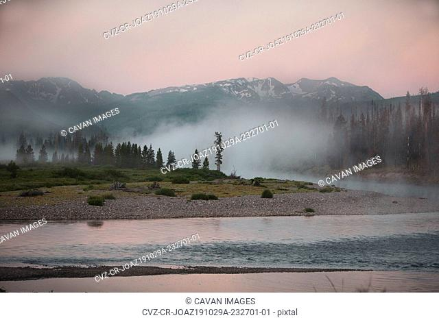 Mist rises over the Upper Snake River in the John D. Rockefeller Jr. Memorial Parkway with the Teton Mountains in the background