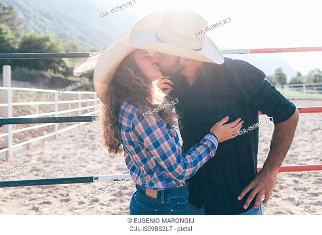 Young cowgirl and boyfriend kissing in rural equestrian arena