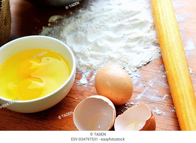 Kitchen rolling pin, eggs and flour on wooden background