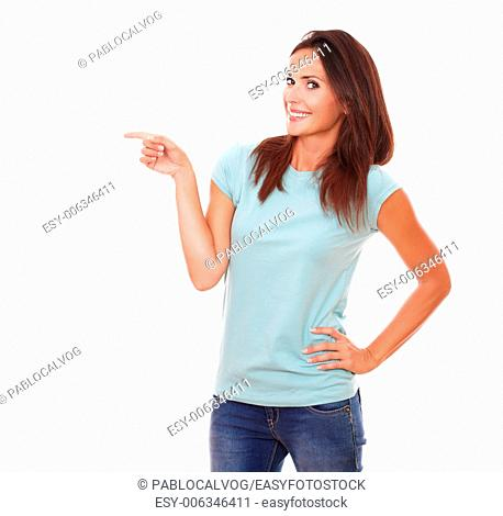Portrait of pretty adult woman on blue t-shirt and blue jeans pointing to her right while standing and smiling at you on isolated white background - copyspace