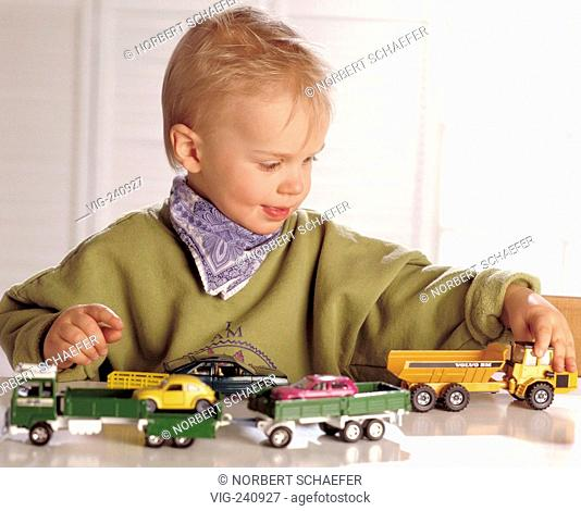 portrait, blond boy, 4 years, wearing olive coloured sweater and neckerchief plays with matchbox cars on a table  - GERMANY, 25/05/2003