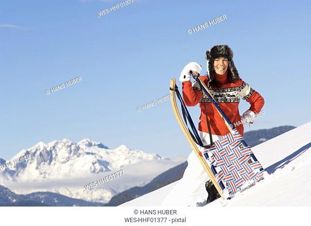 Woman in mountains with sledge