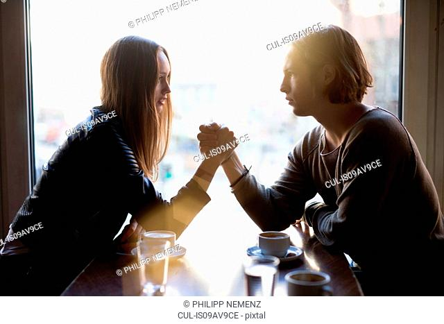 Silhouetted woman and young man holding hands over cafe table