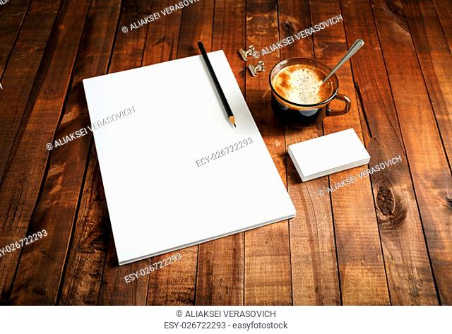 Paper, letterhead, coffee cup and pencil on wooden table background. Mock-up for branding identity. Blank template for design portfolios. Top view