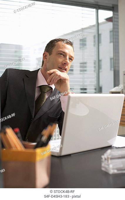 Mature man sitting in front of a laptop