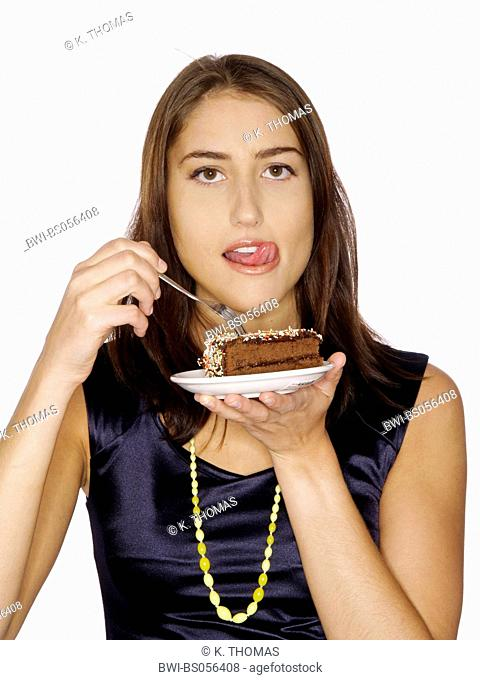 young woman / twen, holding a plate with a peace of cake in her hand, looking at it with desire, licking her chops, looking at the camera