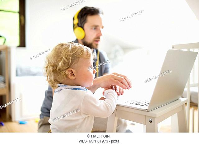Father at home with his little son using laptop
