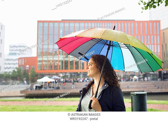 Woman standing under colorful umbrella, concert in background