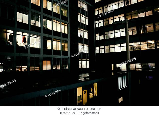 Office building at night with lights in windows and man looking through window. Waterloo, London, England