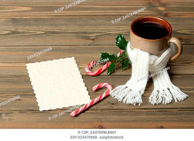Mug Of Hot Tea Or Coffee With Scarf. Empty Card. Christmas Decorations. Space for Text. Wooden Background