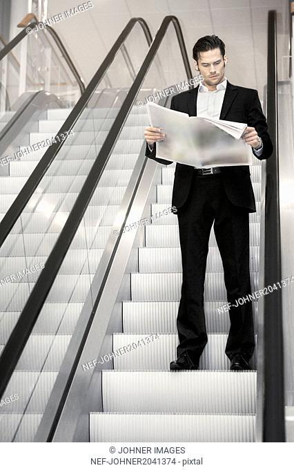 Business on escalator reading newspaper