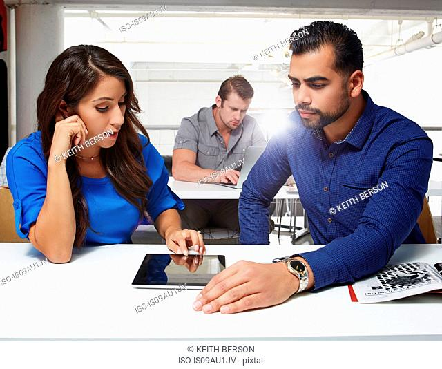 Businesswoman and businessman sitting at desk, looking at digital tablet