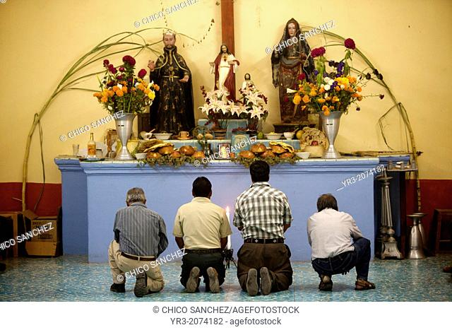 Men pray as they kneel in front of an altar during the Day of the Dead celebrations in Teotilan del Valle, Oaxaca, Mexico