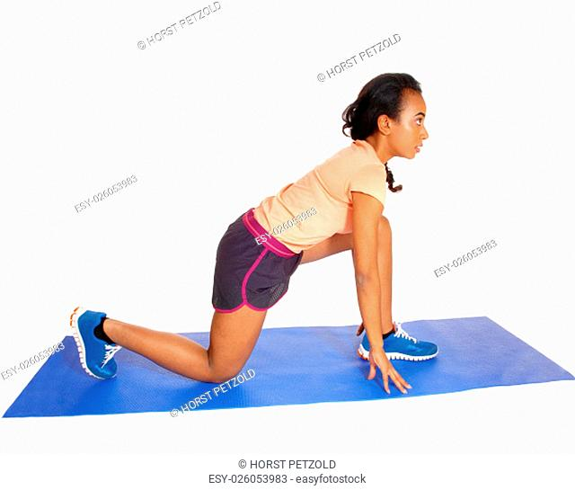 A young African American girl kneeling on a blue yoga mat, in sportswear.isolated for white background.