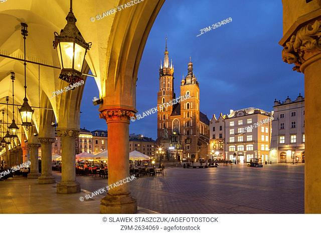 Night falls at the Cloth Hall in Krakow old town, Poland. Looking towards St Mary's church. UNESCO world heritage site