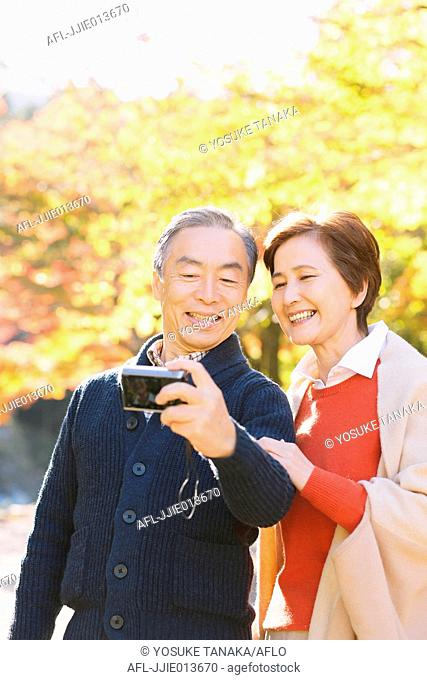 Senior Japanese couple taking selfie in a traditional park in Autumn