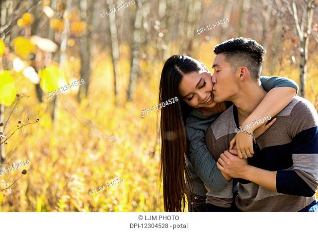A young Asian couple enjoying quality time together outdoors in a park in autumn and embracing and kissing each other in the warmth of the sunlight; Edmonton