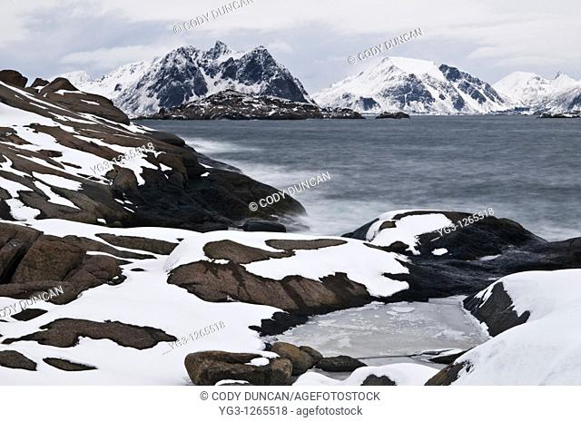 Rocky snow covered shoreline near Stamsund, Vestvågøy, Lofoten Islands, Norway