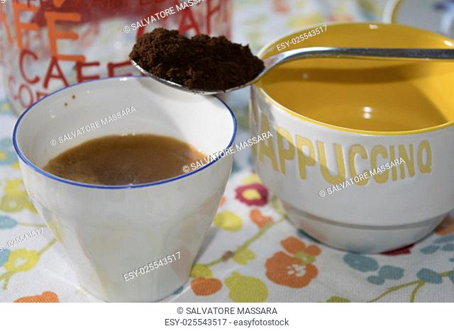 a cup of extra strong coffee with a teaspoon of grounf coffee