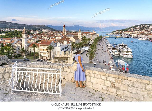 Woman admiring the old town and seafront from Karmelengo castle, in summer. Trogir, Split - Dalmatia county, Croatia
