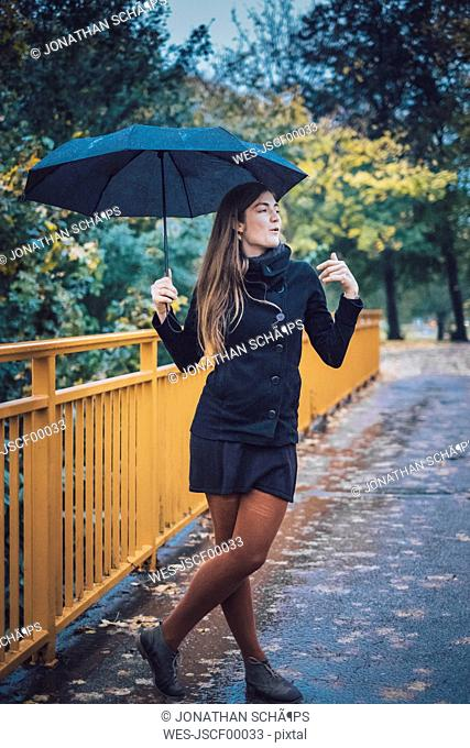 Young woman with umbrella standing on a bridge in autumn