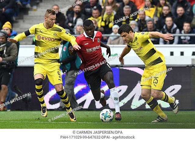 Dortmund's Sokratis Papastathopoulos (r) and Andrij Jarmolenko (l) and Hanover's Ihlas Bebou (l) in action during the Bundesliga soccer match between Hanover 96...
