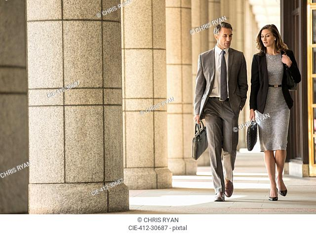 Corporate businessman and businesswoman walking and talking in cloister