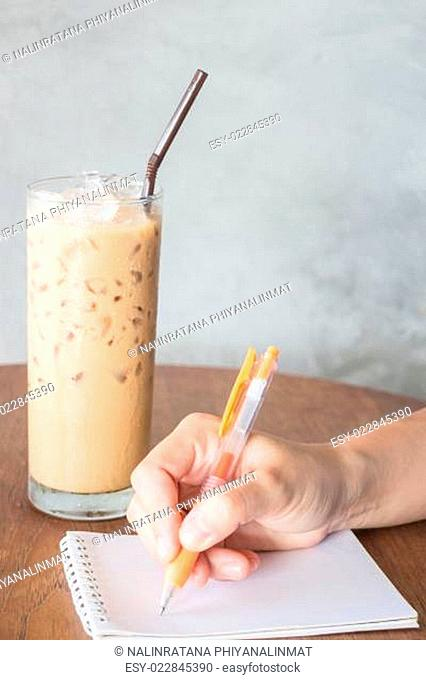 Hand writing on note paper in coffee shop