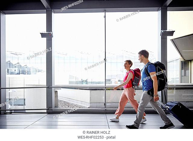 Smiling couple walking at the airport