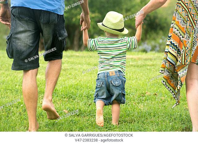 A family walking in the garden barefoot, holding hands