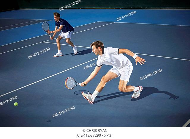 Young male tennis doubles players playing tennis, reaching with tennis racket on blue tennis court