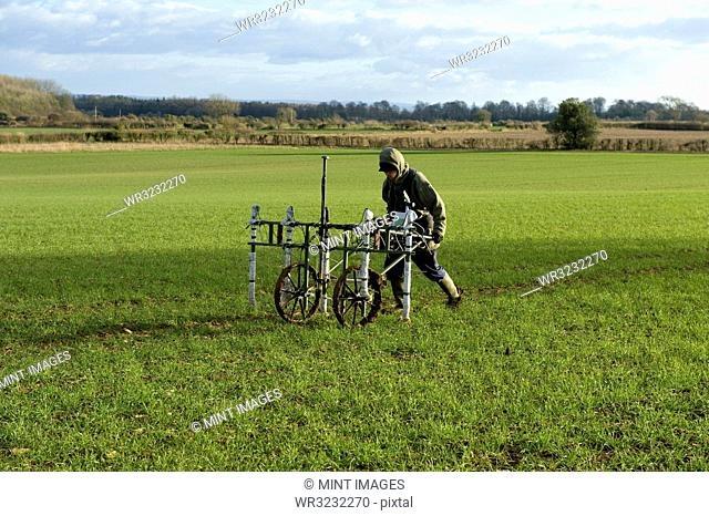 A geophysicist pushing a trolley with ground mapping sensors, creating a geophysical survey of the subsoil in a field
