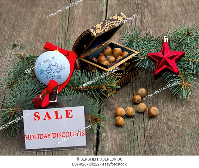 fir-tree branch with an ornament, a casket with nutlets and a label Festive Sale, on a wooden table, a subject holidays Christmas and New Year