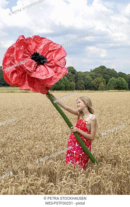 Smiling girl standing on a field with oversized red artificial flower