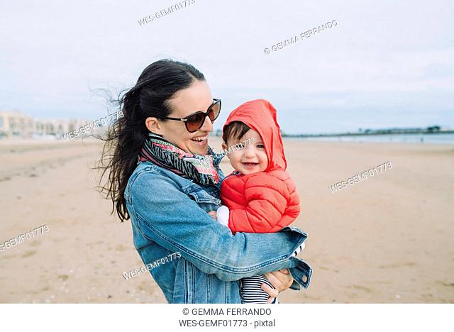 Portrait of smiling baby girl on her mother's arms on the beach