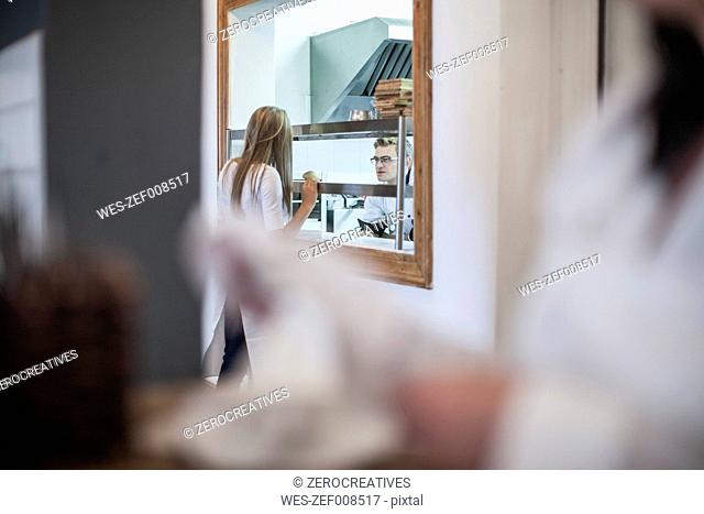 Waitress picking up food from the kitchen