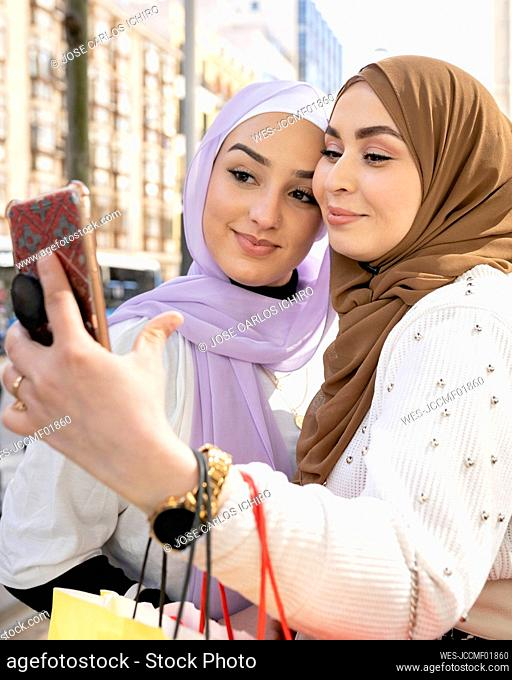 Arab female friends taking selfie through smart phone while shopping