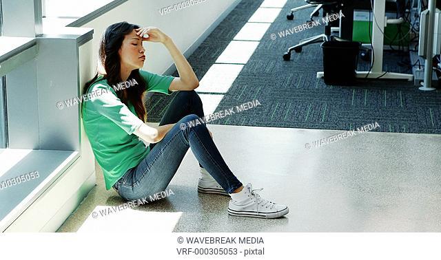 Depressed female executive sitting on the floor