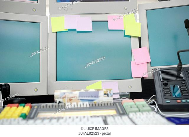 Desk area and computer monitor with sticky notes on it