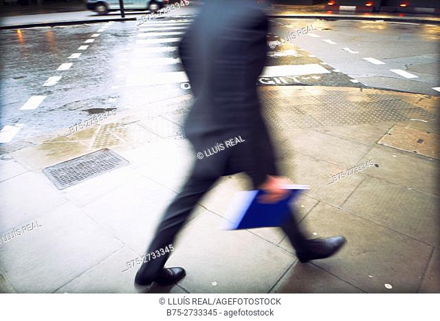 Unrecognizable executive with blue folder walking hurriedly under the rain. London, England
