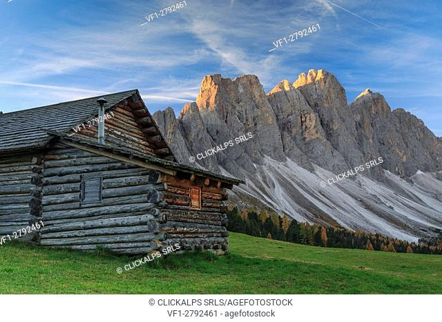 The early morning light illuminates Malga Gampen and the Odle in background. Funes Valley South Tyrol Dolomites Italy Europe