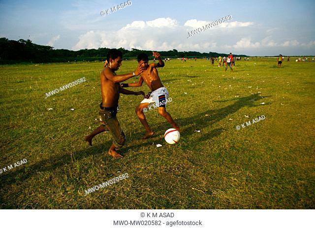 A football match on the bank of the Padma river at Mawa in Dhaka, Bangladesh June 26, 2009