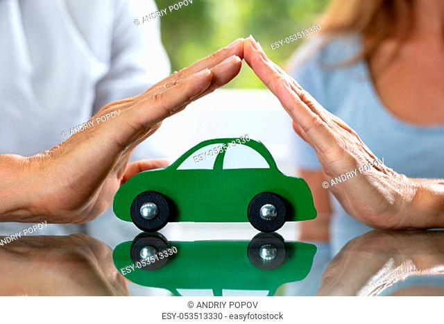 Close-up Of Couple's Hand Protecting Green Wooden Car Over Reflective Desk