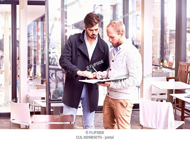 Two young businessmen meeting in cafe writing in notebook